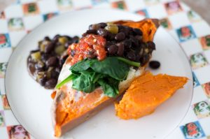 sweet potatos are an easy meal to cook while you're traveling, this sweet potato has an egg baked into it, and is topped with black beans and spinach